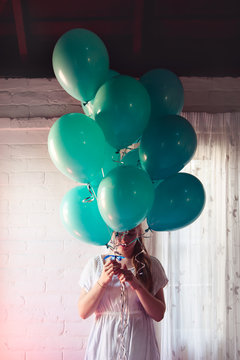 Girl with a bunch of birthday balloons