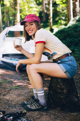 Portrait of a smiling woman drinking coffee at a camp site.