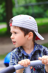 Adorable little 3 year old boy having fun on playground, child wearing reversed cap. Happy boy playing in playground on birthday party in kids amusement park or outdoor play center. Child having fun.