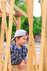 Curious child wearing reversed cap has fun in asian playground landscape, behind the bamboo sticks. Cute boy playing in public park with asian exotic installations. Beautiful 3 year old kid.