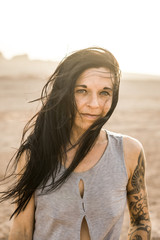 portrait of a black haired, tattoed woman with wind blown hair in the desert