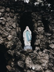 mother mary catholic christian symbolism statue in rock on hillside