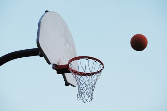 Low angle view of basketball and basketball hoop against clear sky