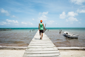 Young Man Walks on an Old Wooden Dock