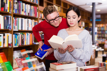 Positive student choosing book in library