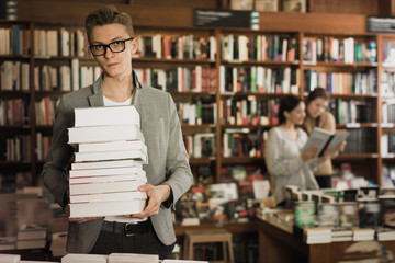 Portrait of serious young man with stack of books in hands in bo