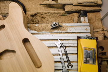 Unfinished electric guitar body next to wrenches