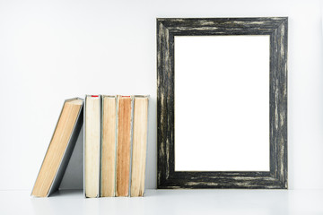 empty black frame and old books on a white background.