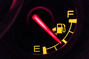 Gasoline gauge display half full of fuel. The dashboard lit up in orange and red light