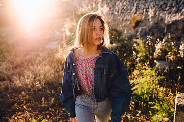 Beautiful young blonde woman with sunlight behind