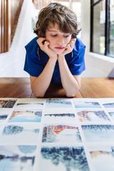 Boy looking at photo prints of a winter vacation