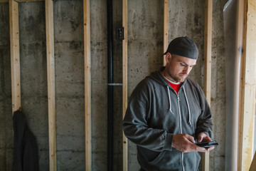 Electrician man using mobile cell phone on jobsite