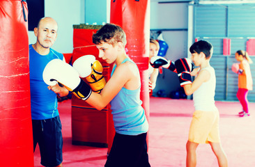 Boxing instructor and young children practicing blows