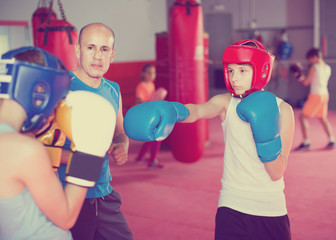 Boxing instructor closely follows the teenagers in sparring