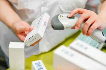 Pharmacist scanning barcode of medicine drug in a pharmacy drugstore.