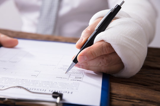 Man With Broken Arm Filling Health Insurance Claim Form