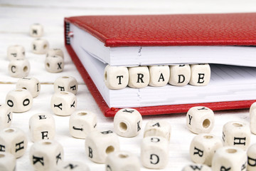 Word Trade written in wooden blocks in notebook on white wooden table.