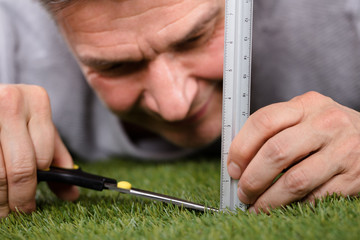 Man Using Measuring Scale While Cutting Grass