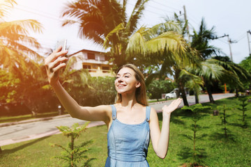 bright portrait of young woman talking video call phone and smiling on green palms background with sunshine. Concept of international travel to Thailand and new technologies