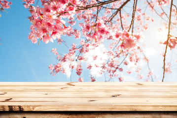 Wall Mural - Top of wood table empty ready for your product and food display or montage with pink cherry blossom flower (sakura) on sky background in spring season.