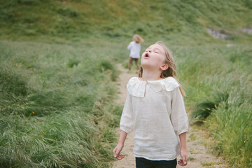 Girl howling into the wind while standing in grassy field