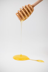 Honey is dripping from the wooden spoon.