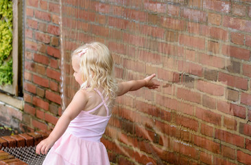 little girl reaching her hand into waterfall wall touching water