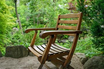 closeup of an old wooden chair sitting in japanese zen garden