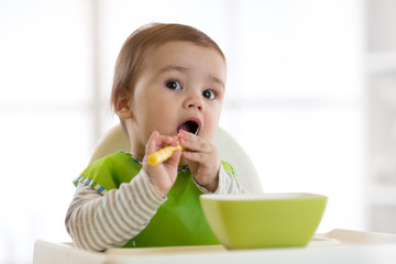 Baby child eats food himself with spoon. Portrait of happy kid boy in high chair.