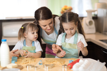 Mom with her 2 and 5 years old daughters are cooking in the kitchen to Mothers day