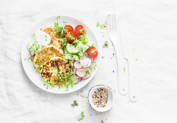 Ricotta zucchini fritters and fresh vegetables salad. Cucumbers, cherry tomatoes, radishes, micro greens and zucchini pancakes on light background, top view. Dietary breakfast or snack