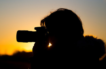 A girl is taking pictures with a camera at sunset