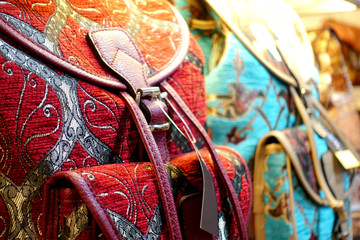 Traditional Turkish crafts. Close-up of colorful embroidered textile backpacks and bags with oriental ornament