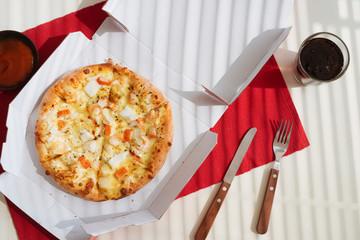 Pizza in a cardboard box on white table. Pizza delivery. Pizza menu.