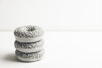 Donut with sprinkles on the rustic wooden background. Selective focus. Black and white image.