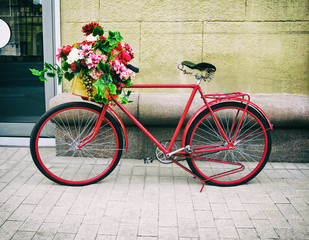 Red bicycle with floral basket lean against the wall in the street. Retro old-fashioned style