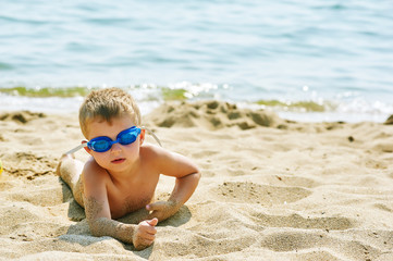 boy with glasses for swimming resting lying on the shore