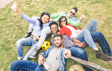 Multiracial best friends taking selfie at meadow picnic - Happy friendship fun concept with young people millennials having fun together outddors on spring summer time - Neutral afternoon filter