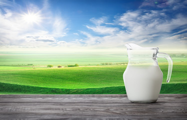 Jug of fresh milk against background of wavy pasture