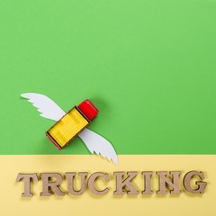 Abstract picture of a truck with wings and a word of trucking. Cargo transportation of the future.