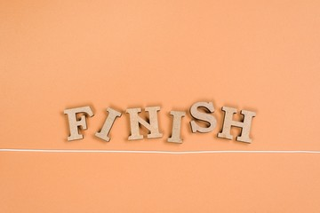Word finish with wooden letters and finish line on an orange background