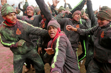 Indian Border Security Force soldiers, with faces smeared with coloured powder, dance during Holi celebrations in a camp in Humhama on the outskirts of Srinagar