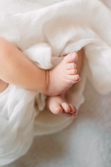 Cute newborn girl sleeping on furry cloth wearing white headband
