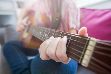Female hands playing acoustic guitar