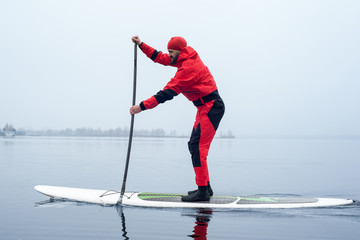 athletic man stand up paddle board