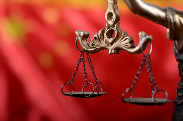 Scales of Justice, Justitia, Lady Justice in front of the flag of China in the background.