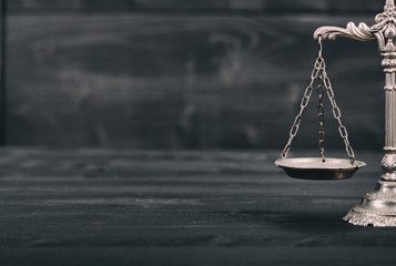 Scales of Justice on a black wooden background.