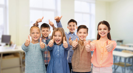 happy students showing thumbs up at school