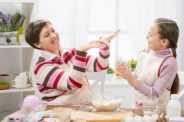 mother and daughter make dough for buns and play with flour, home kitchen interior, healthy food concept
