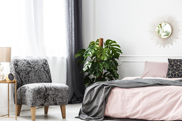 Patterned armchair in cozy bedroom